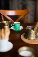 Small cup of coffee surrounded with vintage brass coffee pot, milk jug and sugar can. Tilt-shift and selective focus.