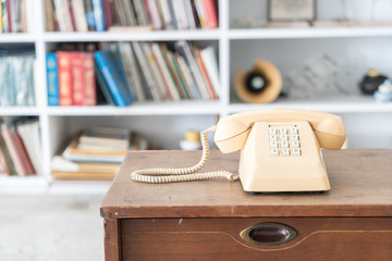 vintage phone on wooden table, on bookshelf background
