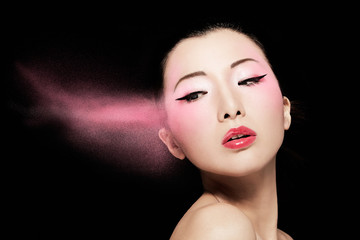 Asian beautiful woman with pink powder flying isolated on black background. Makeup cosmetic beauty image.