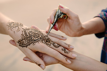 applying henna tattoo on women hands