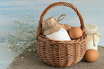 Eggs and dairy products. Basket with eggs and a bottle of milk on a napkin of burlap on a blue wooden background.