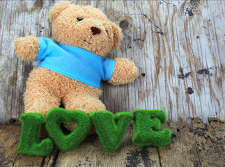 toy bear and words of love with old wood background