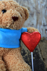 Toy bear and red heart on a dark wooden surface