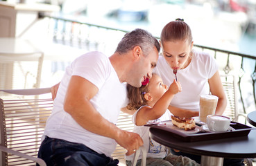 Girl with parents at a cafe