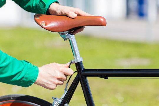 close up of man adjusting fixed gear bike saddle
