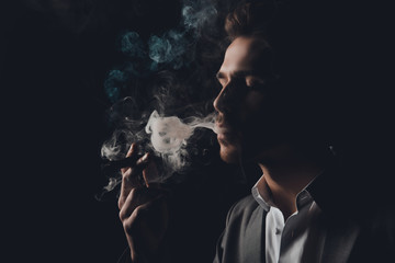 Handome cheeky man in suit on the black background smoking a cig