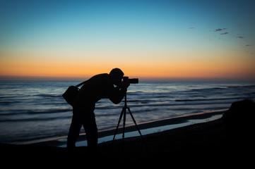 Silhouette of a photographer at sunrise sun