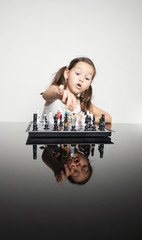 Adorable little girl concentrated playing chess