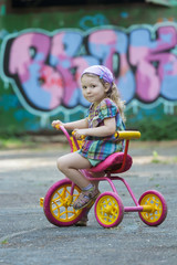 Two years old girl wearing checked tunic and purple bandanna riding yellow and pink tricycle