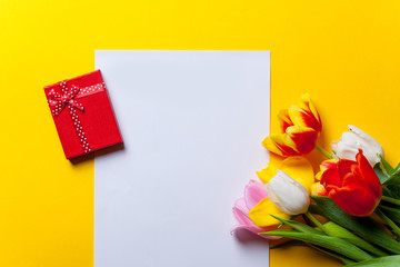 tulips and paper with gifts on yellow