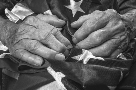 Old woman's hands holding an American flag.