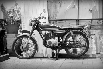 Old motorcycle / Old classic motorcycle parked on sidewalk. Black and white tone.