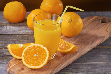 Orange juice on wooden table with sliced fruits
