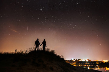 couple standing on the background of a starry sky, a couple standing on the background of the city at night, silhouettes against the stars
