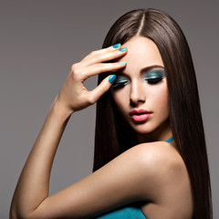Beautiul elegant woman with turquoise make-up and nails. Straigh