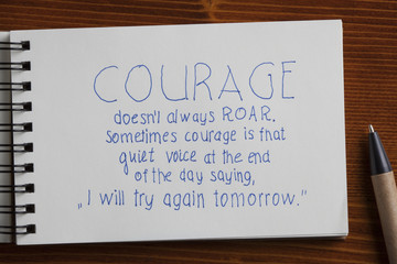 Courage handwritten text on a notebook with pen