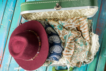 full suitcase on a distressed blue background