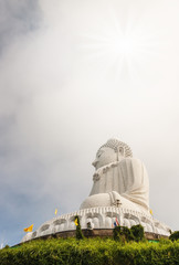 Big buddha in blurred sky and over light the sun