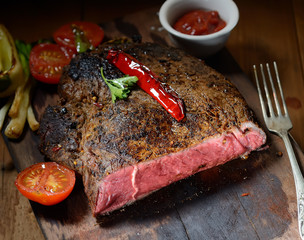 steak on the wooden background with roasted vegetables