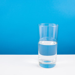 Half empty or half full glass of water on white table. (For positive thinking when see the glass is half full.)