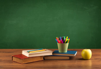 School items on desk with empty chalkboard