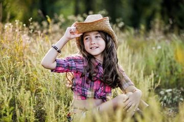 little girl sitting in a field wearing a cowboy hat
