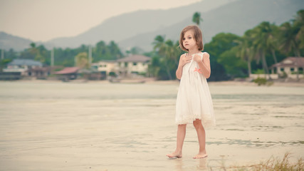 Young happy girl in white dress is walking on the tropical beach