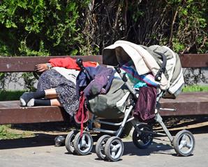 Homeless woman sleeps on a park bench
