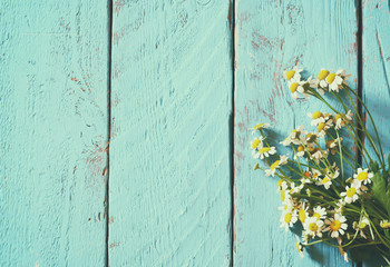 top view image of daisy flowers on blue wooden table. vintage filtered and toned