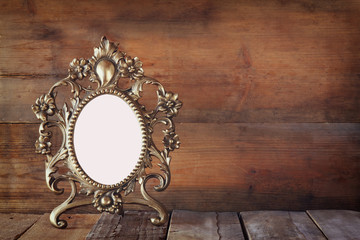 Antique blank victorian style frame on wooden table. vintage filtered image. template, ready to put photography