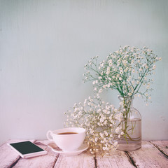 vintage filtered and toned image of smart phone, cup of coffee next to spring white flowers