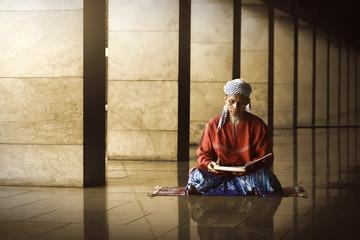 Religious muslim man reading holy koran