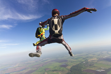 Girl and guy skydivers in freefall in the clouds.