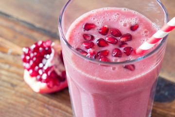 pomegranate smoothie on wooden background