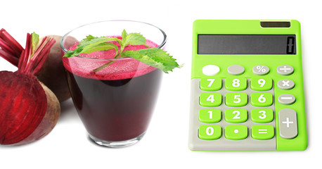 Calculator and fresh beet juice isolated on white