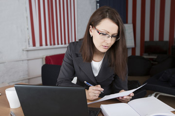 the woman works at office with the laptop