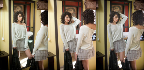 Young woman in white blouse and gray short tutu skirt looking into large mirror holding black leather jacket. Beautiful curly dark hair girl posing in front of wall mirror. Fashionable brunette model.