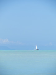 Sailboat cruising beautiful turquoise waters of the Caribbean