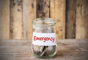 Coins in glass money jar with emergency label, financial concept