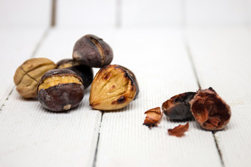 hot toasted chestnuts on white wooden background