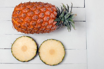 Fresh azores pineapple fruit isolated on a white wooden backgrou