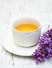 Cup of tea and lilac flowers