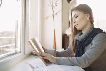 Woman reading a book near the window
