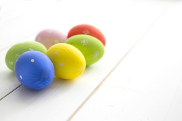 Easter eggs painted on a white wood background