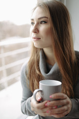 Attractive young woman sitting in a coffee shop at window