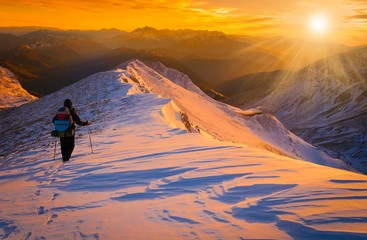 Beautiful amazing sunset winter mountains.  A man goes a sport hike in snow holidays. Christmas background. Unique landscape. Northern country Russia Caucasus.