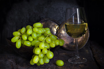 Green grapes and a glass of white wine on dark background - vintage, moody style