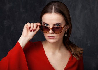 Woman is looking over the sunglasses, gray background