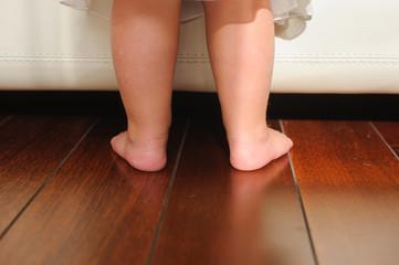 Children's bare feet, beside to bed