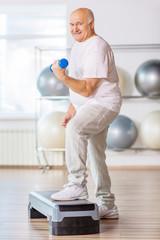 Pleasant senior man practicing step aerobics